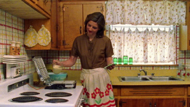 Medium shot REENACTMENT woman approaching kitchen counter, pouring batter into waffle iron and exiting