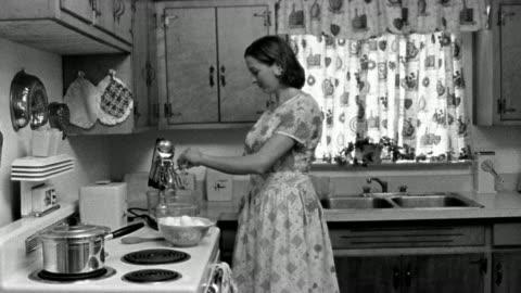 vídeos y material grabado en eventos de stock de medium shot reenactment woman breaking eggs into mixer bowl in kitchen, then exiting - cocina doméstica