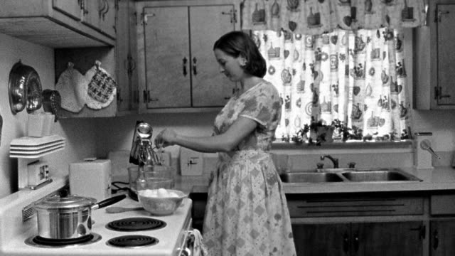 medium shot reenactment woman breaking eggs into mixer bowl in kitchen, then exiting - 1950 stock-videos und b-roll-filmmaterial