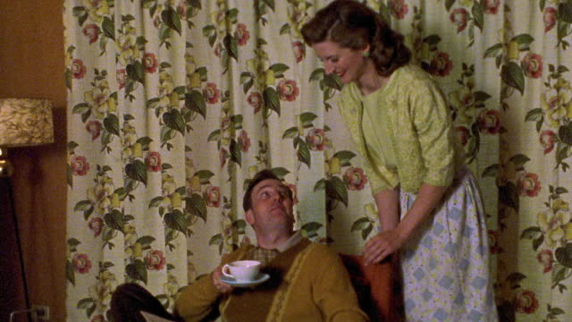 medium shot reenactment woman bringing cup of coffee to man with pipe sitting in living room, then discussing magazine - ボング点の映像素材/bロール