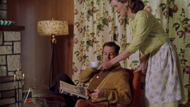 vídeos de stock e filmes b-roll de medium shot reenactment woman bringing cup of coffee to man with pipe sitting in living room, then discussing magazine - 1950