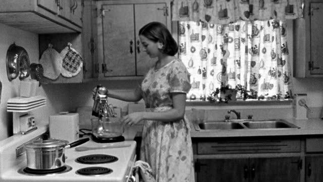 vídeos de stock e filmes b-roll de medium shot reenactment woman entering kitchen and turning on electric mixer - cozinha doméstica