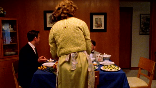 medium shot reenactment woman places ham on dinner table with seated family, then man leads family in saying grace - stay at home mother stock videos & royalty-free footage