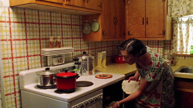 Medium shot REENACTMENT woman removing roast from oven in kitchen, placing it on counter and presenting it with wave of hand