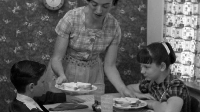 Medium shot REENACTMENT woman serving plates of sandwiches to boy and girl at kitchen table