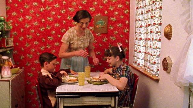 Medium shot REENACTMENT woman serving sandwiches to boy and girl at kitchen table, then pouring milk from pitcher