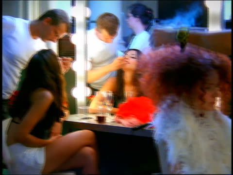 stockvideo's en b-roll-footage met medium shot reflection in mirror of makeup artist putting lipstick on model who laughs / second model in foreground - kleedkamer coulissen