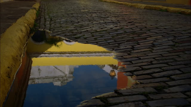 medium shot reflection of colorful building in puddle on brick road / zoom out wide shot view of building / puerto rico - cobblestone stock videos & royalty-free footage