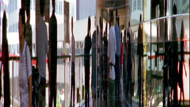 medium shot reflections on mirrored surface of people walking - large group of people stock videos & royalty-free footage