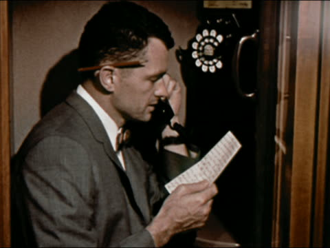 1964 Medium shot reporter in phone booth having conversation on phone while reading from paper / AUDIO