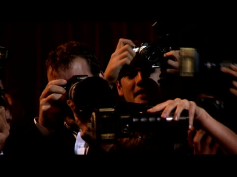 medium shot reporters and paparazzi on red carpet/ london, england - kamera blitzlicht stock-videos und b-roll-filmmaterial