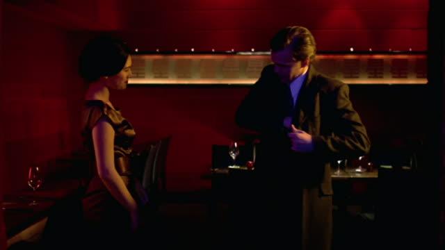 medium shot restaurant hostess giving man his coat/ man leaving - gratuity stock videos & royalty-free footage
