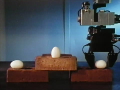 1984 medium shot robotic arm picking up egg and placing next to other egg on arrangement of bricks / AUDIO