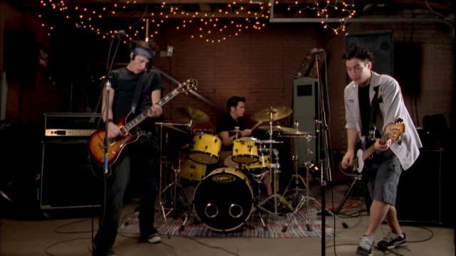 medium shot rock band w/three men performing / bassist jumping - rocking stock-videos und b-roll-filmmaterial