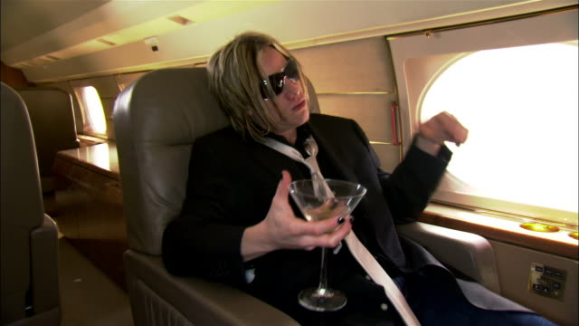 medium shot rock star drinking martini on private airplane - zurücklehnen stock-videos und b-roll-filmmaterial