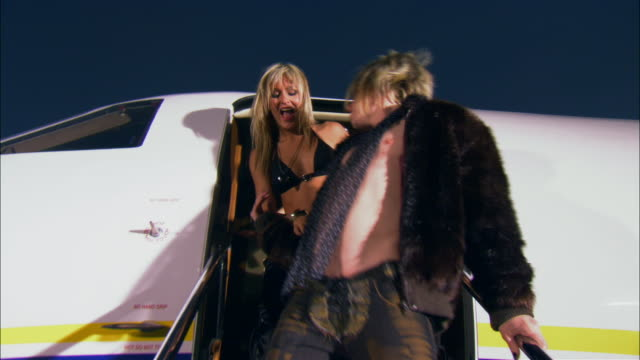Medium shot Rock star exiting private airplane with two groupies / Long Beach, California, USA