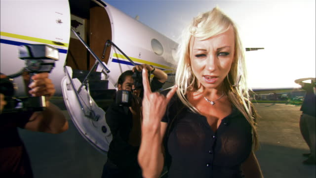 Medium shot Rock star posing and shaking hair toward paparazzi photographers near private airplane / Long Beach, California, USA
