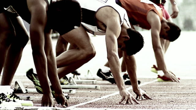 Medium shot runners taking places in starting blocks before race