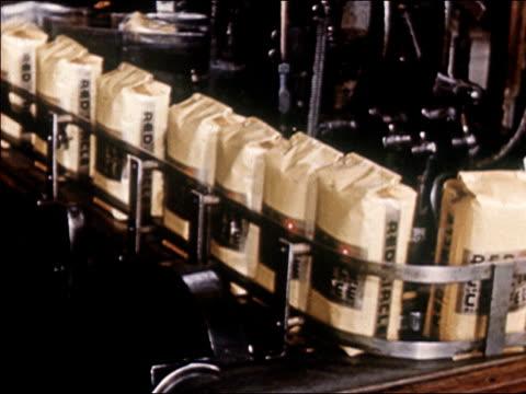 vidéos et rushes de 1954 medium shot sacks of red circle coffee on moving on conveyor belt / audio - 1954