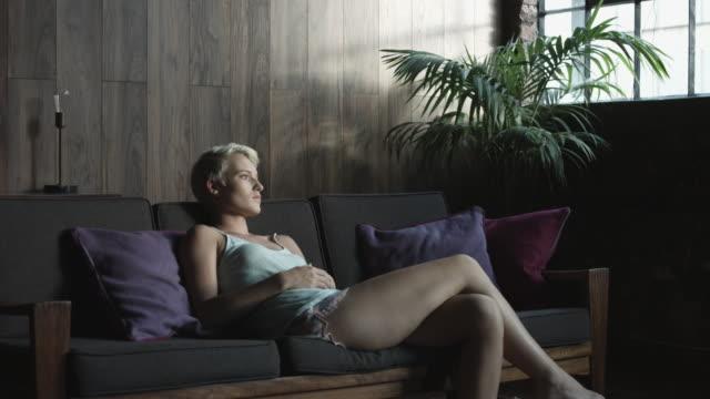 medium shot, sad blonde woman on couch - kamisol stock-videos und b-roll-filmmaterial