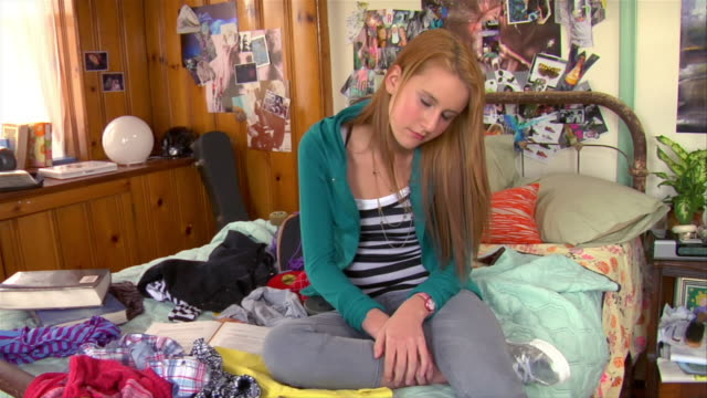 vidéos et rushes de medium shot sad teenage girl sitting on bed in bedroom / brooklyn, new york, usa - messy bedroom