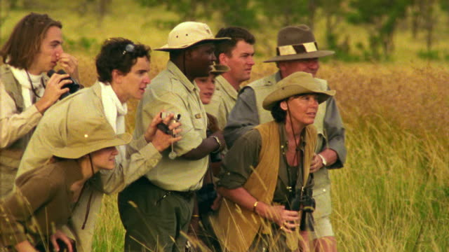 Medium shot safari guide points and group of people kneel in grass + watch something offscreen/ South Africa
