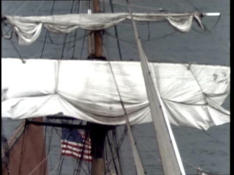 vídeos de stock e filmes b-roll de medium shot sail being lowered on sailing ship - baixar