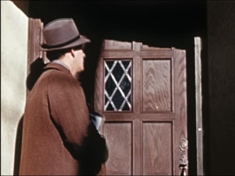 1941 medium shot salesman at door and woman answering it + greeting him / salesman taking hat off - door to door salesperson stock videos & royalty-free footage