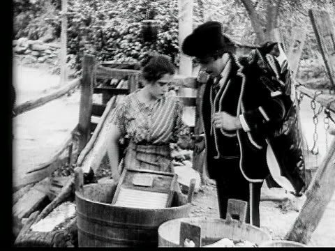 stockvideo's en b-roll-footage met 1910 b/w medium shot salesman flirting with maid in yard by giving her ring  - 1900 1909