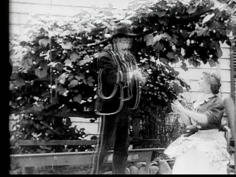 stockvideo's en b-roll-footage met 1910 b/w medium shot salesman selling fabric to housewife  - 1900 1909