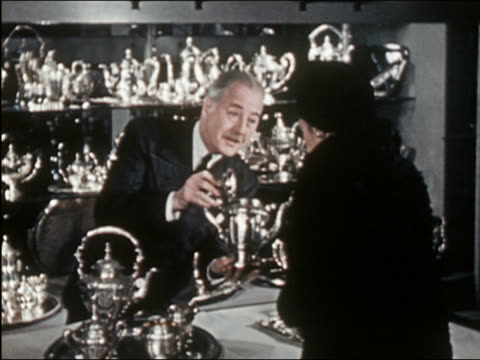 1941 medium shot salesman showing silver teapots to female customers - salesman stock videos and b-roll footage