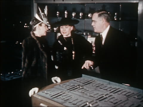 1941 medium shot salesman showing silverware to two women - male with group of females stock videos & royalty-free footage