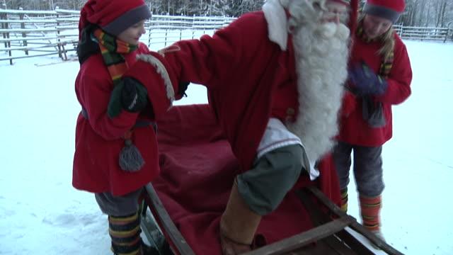 vídeos de stock e filmes b-roll de medium shot santa claus in his land of rovaniemi getting on his sledge shot on november 2010 - mamífero ungulado