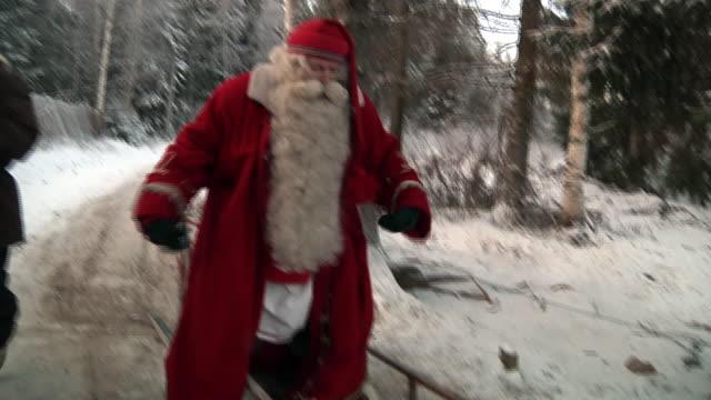 vídeos de stock e filmes b-roll de medium shot santa claus in his land of rovaniemi saying goodbye while sitting down on his sledge shot on november 2010 - mamífero ungulado