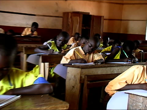 Medium shot schoolboy writng in classroom/ zoom out medium shot pan schoolchildren writing/ Ghana