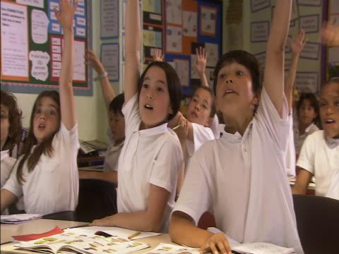 Medium shot schoolchildren in classroom raising hands/ London, England