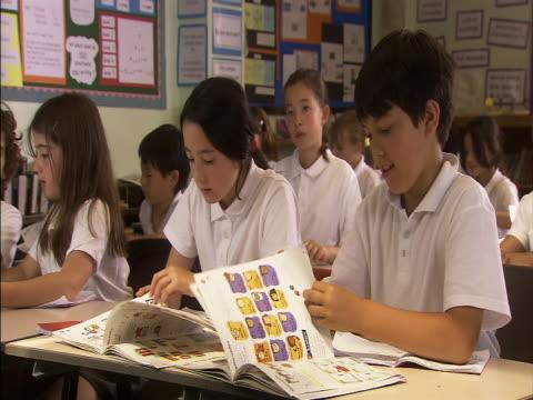 vídeos de stock, filmes e b-roll de medium shot schoolchildren in classroom turning pages in textbook and raising hands/ london, england - 10 11 anos