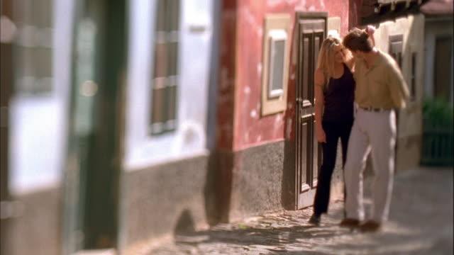 vídeos de stock, filmes e b-roll de medium shot selective focus couple walking up street / prague - de braços dados