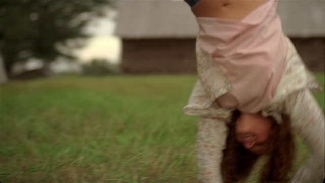 medium shot selective focus girl doing cartwheel in field / barn in background - cartwheel stock videos & royalty-free footage