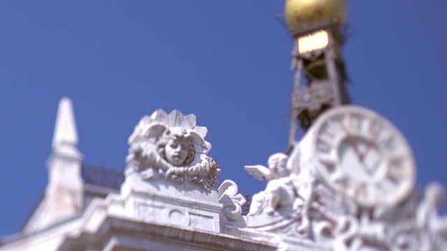 medium shot selective focus pan architectural details and clock on building with tower in background / madrid - madrid stock videos & royalty-free footage