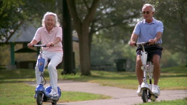 Medium shot selective focus senior couple riding motorized scoooters