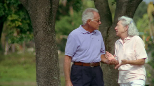 medium shot selective focus senior couple walking together and holding hands / man putting arm around woman - maglietta polo video stock e b–roll