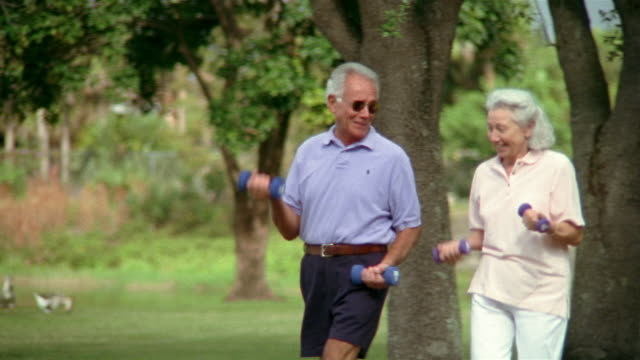 Medium shot selective focus senior couple walking with weights and talking