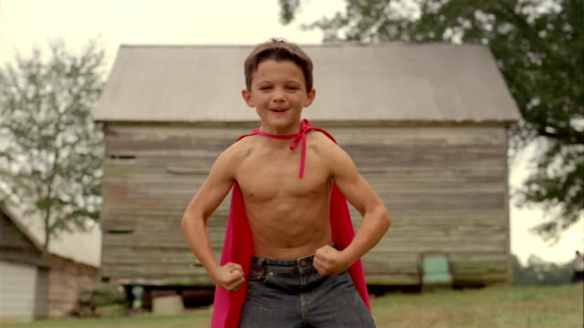 Medium shot selective focus shirtless boy wearing a red cape / flexing muscles and making faces