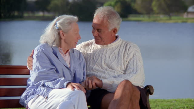 Medium shot selective focus slow motion senior couple holding hands and kissing on bench with lake in background