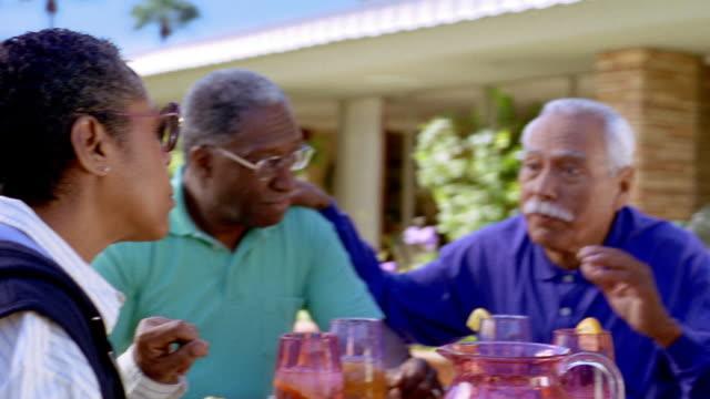 medium shot senior black couple and senior hispanic couple talking, sitting at patio table outdoors / arizona - kopfbedeckung stock-videos und b-roll-filmmaterial