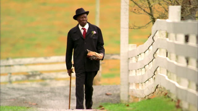 medium shot senior black man in hat and suit walking on country road w/cane - senior men stock videos & royalty-free footage