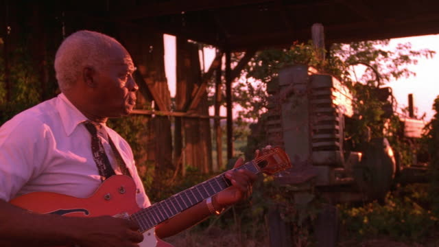 medium shot senior black man playing guitar and singing near old tractor at twillight / tennessee - einzelner senior stock-videos und b-roll-filmmaterial