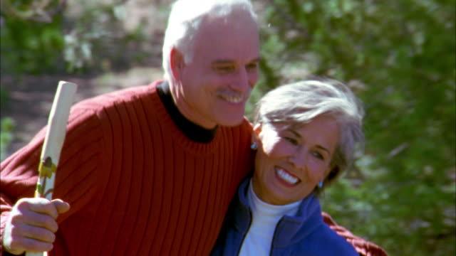 Medium shot senior couple hiking and kissing on park trail