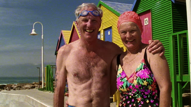 Medium shot senior couple in swimsuits laughing by beach houses / St. James Beach, Cape Town, South Africa